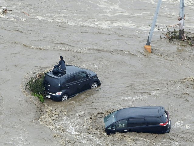 People wait for rescue on the roof of a car (L) and beside a utility pole at an area flooded by the Kinugawa river, caused by typhoon Etau in Joso, Ibaraki prefecture, Japan, in this photo taken by Kyodo September 10, 2015. (Photo by Reuters/Kyodo News)