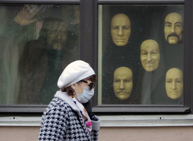 A woman wearing a face mask to protect against coronavirus walks past wax faces displayed in a window of a wax museum in St.Petersburg, Russia, Monday, May 4, 2020. (Photo by Dmitri Lovetsky/AP Photo)