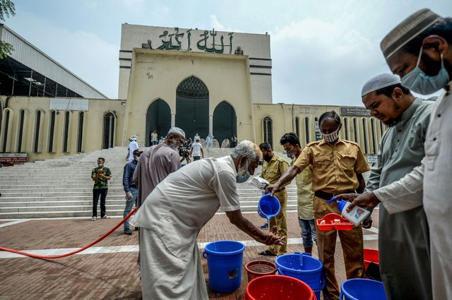 Muslims wash their hands before entering the National Mosque Baitul Mukarram to offer prayers after the government resumed mass prayers easing the lockdown imposed as a preventive measure against the COVID-19 coronavirus during the Muslim holy month of Ramadan in Dhaka on May 7, 2020. (Photo by Munir Uz Zaman/AFP Photo)