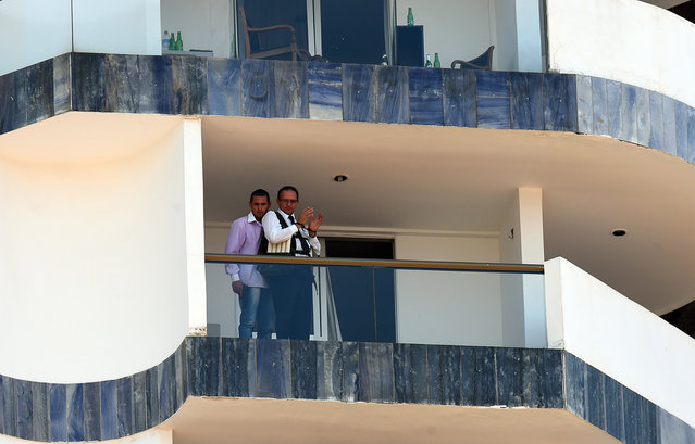An unidentified man (L) keeps a hotel employee with an explosive-laden vest at a balcony of the hotel in Brasilia on September 29, 2014. (Photo by Evaristo Sa/AFP Photo)
