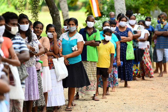 People lineup to collect free food during a nationwide curfew imposed as a preventive measure against the spread of the COVID-19 novel coronavirus, at a temple in Delgoda on May 9, 2020. (Photo by Ishara S. Kodikara/AFP Photo)