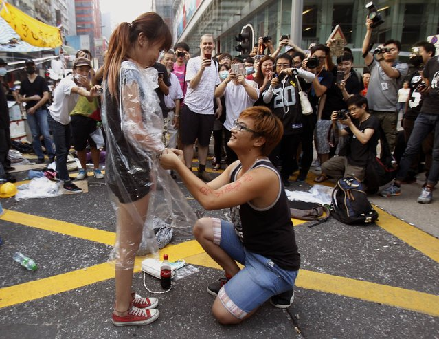 """Yau, 22, gets down to his knees and proposes to his girlfriend Chen, 21, both university students and pro-democracy protesters. on a main street which they occupied, at Mongkok shopping district in Hong Kong October 5, 2014.Tens of thousands of protesters have staged sit-ins across Hong Kong over the past week, demanding the city's pro-Beijing leader Leung Chun-ying step down and calling on China to reverse its decision to select the candidates for the city's 2017 leadership election. Chinese characters on Yau's arm read as """"Leung Chun-ying, step down"""". (Photo by Liau Chung-ren/Reuters)"""