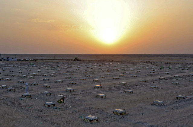 The sun sets over a cemetary for COVID-19 victims, 20 km from the central Iraqi holy city of Najaf, on June 10, 2020. (Photo by Ali Najafi/AFP Photo)