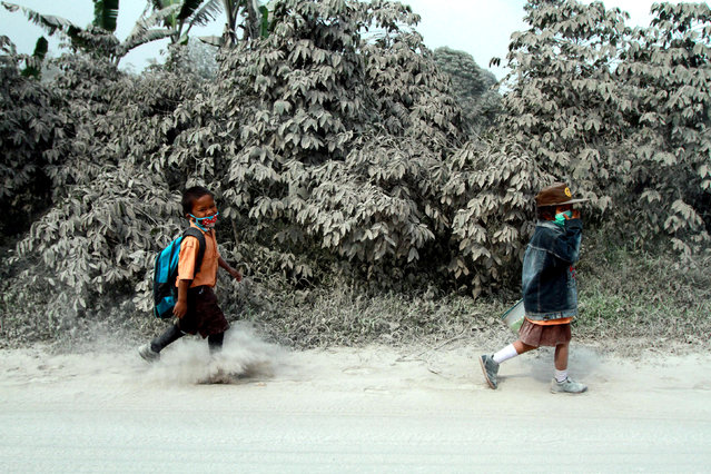 Indonesian students walk on a street covered in Mount Sinabung volcanic ash in Sukandebi village, Karo, North Sumatra, Indonesia, 10 October 2014. (Photo by Dedy Sahputra/EPA)
