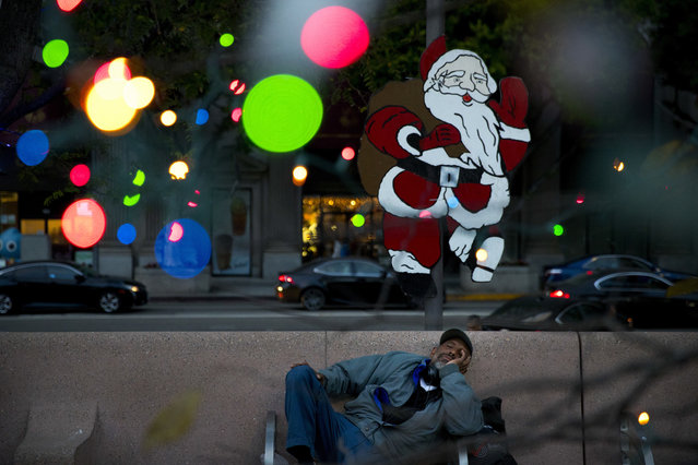 Homeless man Alonzo Harrison, 47, takes a nap on a bench at Pershing Square decorated with Christmas lights in the background on Monday, December 4, 2017, in Los Angeles. A homeless crisis of unprecedented proportions is rocking the West Coast, and its victims are being left behind by the very things that mark the region's success: soaring housing costs, rock-bottom vacancy rates and a roaring economy that waits for no one. (Photo by Jae C. Hong/AP Photo)