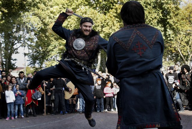 Georgian men in national costumes stage a fight with traditional sabers during a folk festival in Tbilisi, Georgia, Saturday, October 11, 2014. The folk festival was held for the second time in the capital city of Tbilisi. (Photo by Shakh Aivazov/AP Photo)