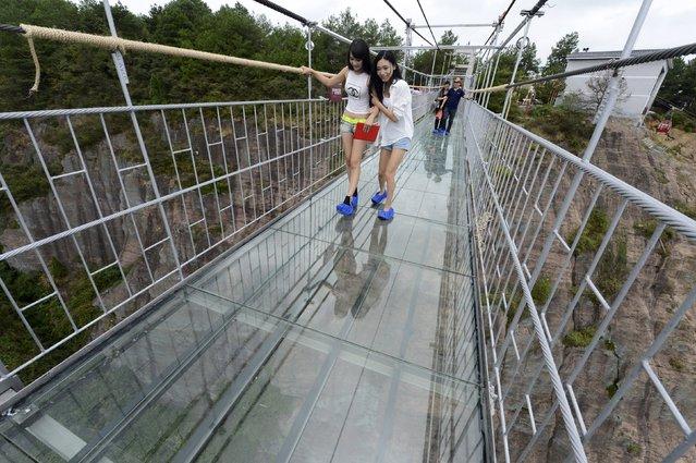 Tourists look down as they walk on a glass suspension bridge at the Shiniuzhai National Geo-park in Pinging county, Hunan province, China, September 24, 2015. The 300-metre-long (984 ft) glass bridge, which opened to tourists for the first time on Thursday, spans over a canyon which is about 180 metre deep (591 ft), local media reported. (Photo by Reuters/China Daily)