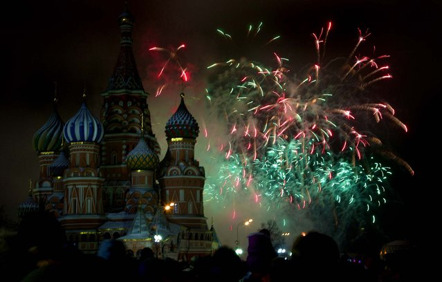 Fireworks explode over St. Basil Cathedral as people celebrate the new year in Moscow's Red Square. (Photo by Ivan Sekretarev/Associated Press)
