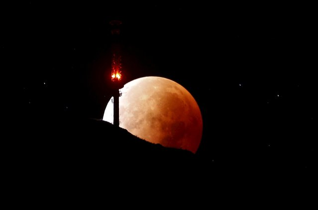 The moon, appearing in a dim red colour, is covered by the Earth's shadow during a total lunar eclipse over the peak of mount Rigi, Switzerland, September 28, 2015. Sky-watchers around the world were treated when the shadow of Earth cast a reddish glow on the moon, the result of rare combination of an eclipse with the closest full moon of the year. (Photo by Arnd Wiegmann/Reuters)