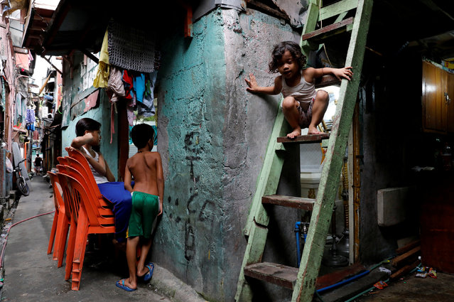 Children attend the wake of Rolando Arellano Campo and Sherwin Bitas inside a house two days after they were killed in a police operation captured on CCTV, in Tondo, Manila on November 27, 2017. (Photo by Dondi Tawatao/Reuters)