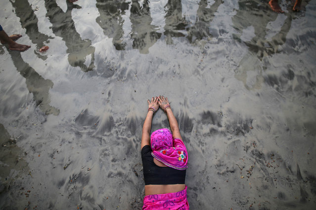 A Hindu devotee lies along the shores of the Arabian Sea as she offers prayers to the Sun god during the Chhat festival in Mumbai October 29, 2014. (Photo by Danish Siddiqui/Reuters)