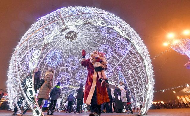 People during New Year celebrations in Oktyabrskaya Ploshchad Square in central Minsk on December 31, 2017. (Photo by Viktor Drachev/TASS via Getty Images)