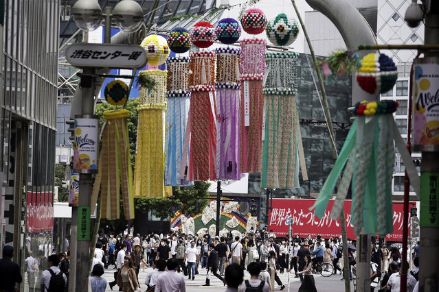 People wearing masks against the spread of the new coronavirus walk at Shibuya pedestrian crossing in Tokyo Friday, July 31, 2020. The Japanese capital confirmed Friday more than 400 new coronavirus cases. (Photo by Eugene Hoshiko/AP Photo)