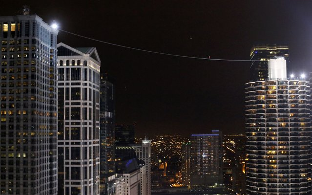 Daredevil Nik Wallenda walks along a tightrope between two skyscrapers suspended 500 feet (152.4 meters) above the Chicago River in Chicago, Illinois, November 2, 2014. (Photo by Jim Young/Reuters)