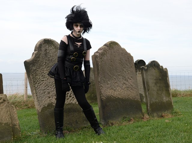 "Abbie Dodsworth, aged 14, from Stockton on Tees sits in the grounds of St Mary's Church during the ""Whitby Goth Weekend"", North Yorkshire, on November 2, 2014. (Photo by Anna Gowthorpe/PA Wire)"