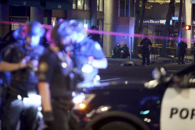 Police gather near where a person was shot Saturday night, August 29, 2020, in Portland, Ore. Fights broke out in downtown Portland as a large caravan of supporters of President Donald Trump drove through the city, clashing with counter-protesters. (Photo by Dave Killen/The Oregonian via AP Photo)