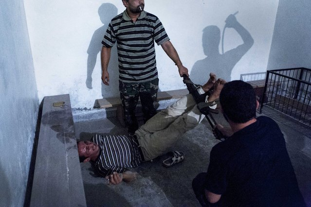 """This picture by Turkish photographer Emin Oezmen won the 2nd Prize Spot News Single for """"Interrogation"""" in the category """"Spot News"""" in the 56th World Press Photo Contest, that was announced by the organizers on 15 February 2013 in Amsterdam, The Netherlands. Opposition fighters regularly launched operations to seize government informants after dark. Two informants were captured, declared guilty under interrogation, and tortured throughout the night; tired soldiers had to be replaced so the torture could continue. After 48 hours, the captives were released. The picture is dated 31 July 2012, in Aleppo, Syria. (Photo by Emin Oezmen/EPA)"""