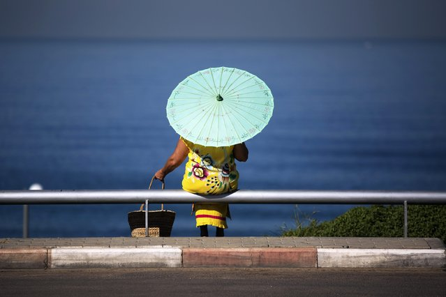 A woman with a parasol sits overlooking the Mediterranean Sea near a beach in Jaffa just south of Tel Aviv  October 22, 2014. (Photo by Finbarr O'Reilly/Reuters)