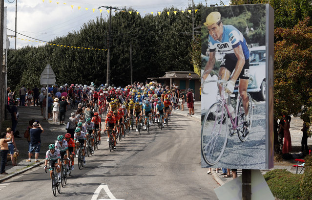 The pack rides past a picture of late French cyclist ace Raymond Poulidor in Saint-Leonard-de-Noblat during the stage 12 of the Tour de France cycling race over 218 kilometers from Chauvigny to Sarran, Thursday, September 10, 2020. (Photo by Thibault Camus/AP Photo)