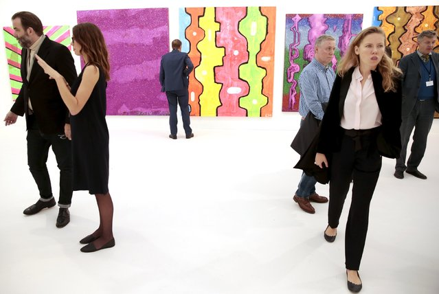 Visitors walk past artwork by Chris Martin at the Frieze Art Fair in London, Britain October 14, 2015. (Photo by Suzanne Plunkett/Reuters)