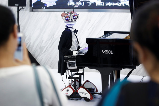 """People watch the robot """"Teo Tronico"""", designed by Matteo Suzzi, play piano and sing popular songs at the 2017 World Robot Conference in Beijing, China August 22, 2017. (Photo by Thomas Peter/Reuters)"""