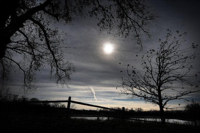 The sun shines through clouds Wednesday morning November 12, 2014, in Salina, Kan. (Photo by Tom Dorsey/AP Photo/Salina Journal)