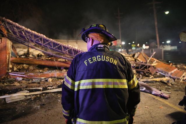 A Ferguson firefighter surveys rubble at a strip mall that was set on fire when rioting erupted following the grand jury announcement in the Michael Brown case on November 25, 2014 in Ferguson, Missouri. (Photo by Scott Olson/Getty Images)