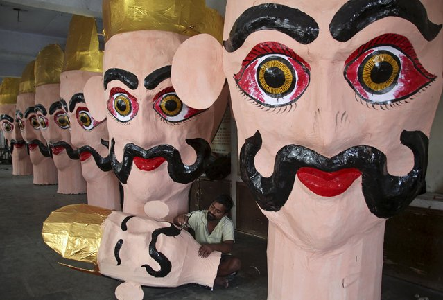 """An artisan paints an effigy of demon king Ravana during preparation for the upcoming Hindu festival of Dussehra in Chandigarh, India, October 15, 2015. Effigies of the 10-headed demon king """"Ravana"""" are burnt on Dussehra, the Hindu festival that commemorates the triumph of Lord Rama over the Ravana, marking the victory of good over evil. Dussehra is on October 22. (Photo by Ajay Verma/Reuters)"""