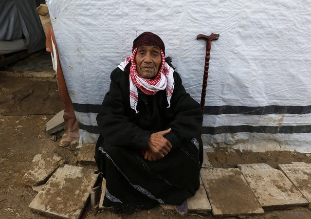 An elderly Syrian refugee woman sits near her tent at a refugee camp in Zahle in the Bekaa valley November 27, 2014. (Photo by Jamal Saidi/Reuters)
