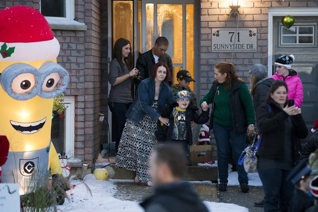 Evan Leversage, who is terminally ill with brain cancer, leaves his house to get a tour of the neighbourhood to see all the Christmas lights with his mother Nicole Wellwood (2nd L, front) in St. George, Ontario, Canada October 24, 2015. (Photo by Mark Blinch/Reuters)