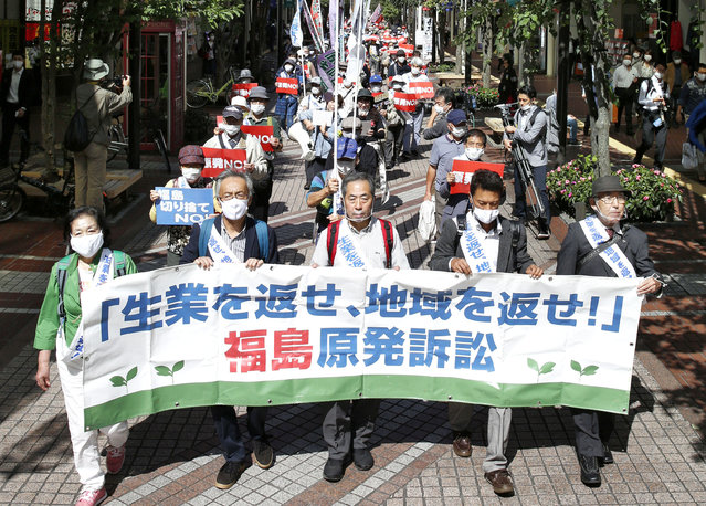 """A group of plaintiffs and supporters march ahead of the Sendai High Court's ruling on the Fukushima Dai-ichi nuclear plant disaster in Sendai, northern Japan, Wednesday, September 30, 2020. The court on Wednesday found negligence by the government and the operator of the wrecked Fukushima nuclear plant in failing to take tsunami measures to prevent the 2011 nuclear disaster, ordering them to jointly pay some 1 billion yen ($9.5 million) in damages to thousands of residents for their lost livelihoods. The banner reads: """"Return jobs, return regions!"""". (Photo by Kyodo News via AP Photo)"""