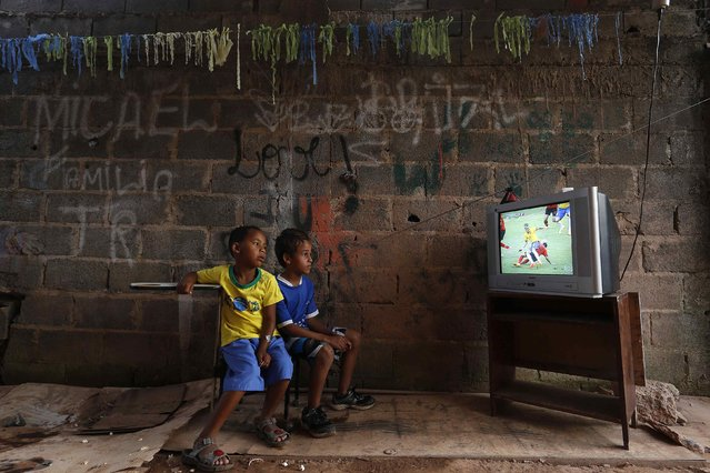 Boys watch a screening of the 2014 World Cup Group A soccer match between Brazil and Mexico, at the slum of Varjao on the outskirts of Brasilia, in this June 17, 2014 file photo. (Photo by Ueslei Marcelino/Reuters)