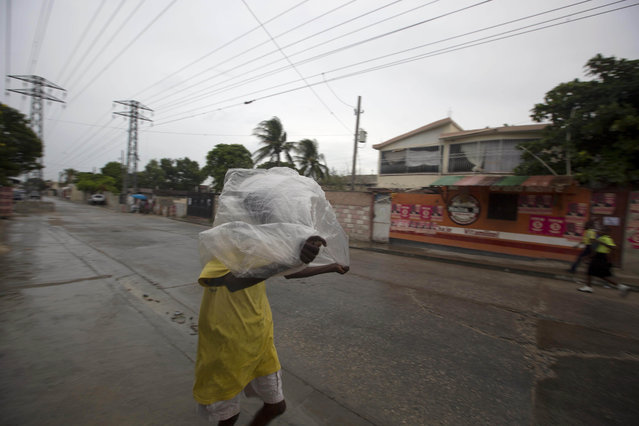A man crosses a street using a garbage bag as protection from a light rain, in Port-au-Prince, Haiti, Monday, October 3, 2016. (Photo by Dieu Nalio Chery/AP Photo)