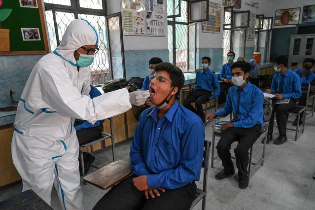 A health official (L) collects a swab sample from a student to test for the Covid-19 coronavirus at a government school in Lahore on October 1, 2020, after the educational institutes reopened nearly six months after the spread of the Covid-19 coronavirus. (Photo by Arif Ali/AFP Photo)