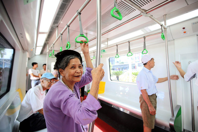 An elderly woman stands inside a model of the skytrain displayed at Giang Vo exhibition center in Hanoi, Vietnam, 30 October 2015. The model is opened to public for people to visit and give feedback before the skytrains are completed in the future. (Photo by Luong Thai Linh/EPA)