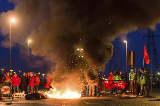 Workers burn tires to block one of the main entrances to the harbour in Antwerp, Belgium, during a first regional strike Monday, November 24, 2014. (Photo by Geert Vanden Wijngaert/AP Photo)