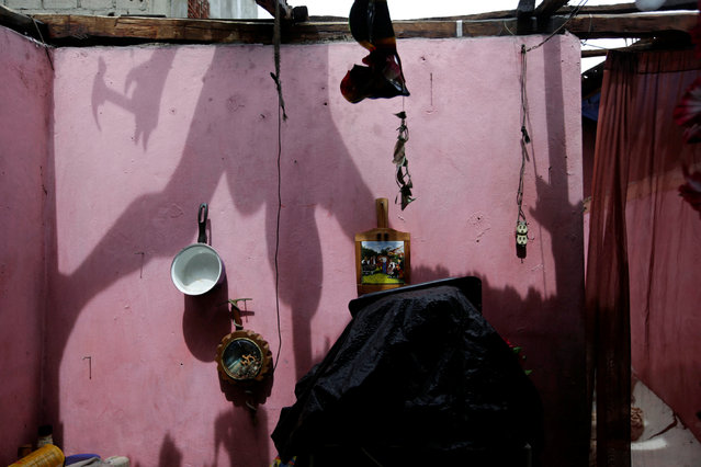 The shadow of a man is casted on a wall as he fixes the roof of a house damaged by Hurricane Matthew in Les Cayes, Haiti, October 5, 2016. (Photo by Andres Martinez Casares/Reuters)