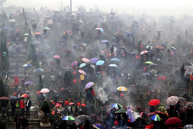Residents burn incense and paper money to pay their respects to the dead as it rains on a smoke filled hillside cemetery in Jinjiang, China,on April 4, 2013. The Qingming Festival or Tomb-Sweeping Day is an annual festival to honor the dead. (Photo by Associated Press)