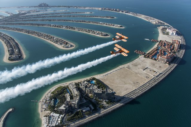 The British Breitling Wingwalkers, Danielle Hughes and Emily Guilding, soar above the Palm Jumeirah in Dubai at 1,500 feet (460 meters) in excess of 100mp/h, ahead of their Dubai debut performance at the 2014 UIM Skydive Dubai XCAT World Powerboating Series, on Saturday, 13th December 2014. (Photo by Katsuhiko Tokunaga/Breitling via AP Images)