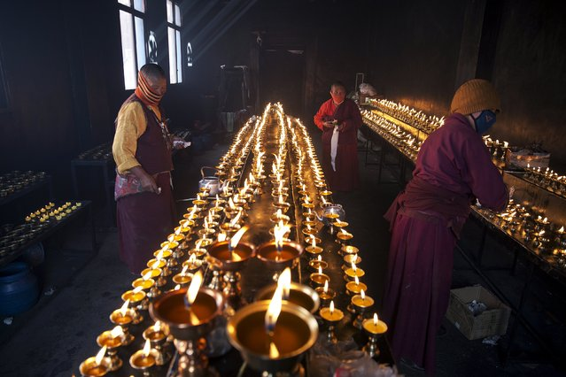Tibetan Buddhist nuns keep yak butter lamps burning at a Buddhist laymen lodge where thousands of people gather for daily chanting session during the Utmost Bliss Dharma Assembly, the last of the four Dharma assemblies at Larung Wuming Buddhist Institute in remote Sertar county, Garze Tibetan Autonomous Prefecture, Sichuan province, China October 30, 2015. (Photo by Damir Sagolj/Reuters)