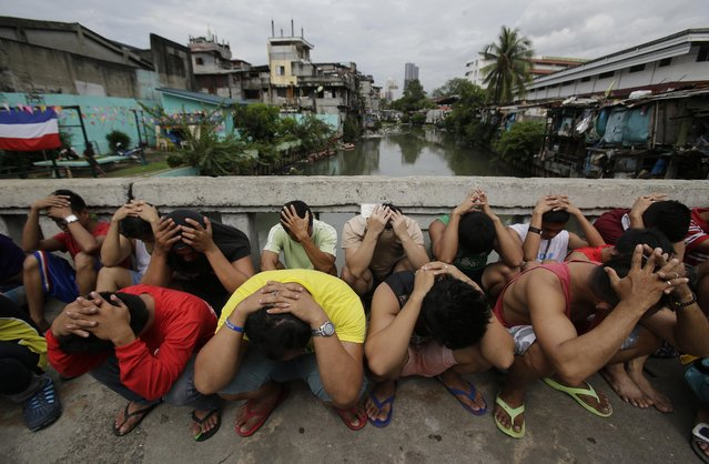 """Filipino men place their hands over their heads as they are rounded up during a police operation as part of the continuing """"War on Drugs"""" campaign of Philippine President Rodrigo Duterte in Manila, Philippines Friday October 7, 2016. An independent poll recently released showed that more than three-quarters of Filipinos are satisfied with President Duterte, even though he is under fire internationally for his deadly crackdown on suspected drug dealers and users. (Photo by Aaron Favila/AP Photo)"""