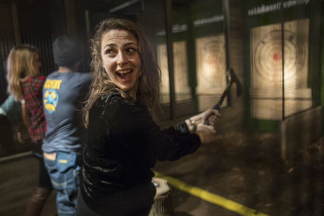 In this Saturday, March 3, 2018, photo, a contestant gets ready to throw a hatchet at a wooden bull's-eye at the Kick Axe Throwing venue in the Brooklyn borough of New York. (Photo by Mary Altaffer/AP Photo)