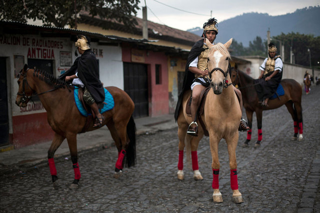 Devotees dressed as Roman soldiers wait on horseback to join the Jesus of Nazareth Good Friday procession in Antigua, Guatemala, Friday, March 30, 2018. Residents of Antigua turn their town into a biblical Jerusalem complete with Roman soldiers on horseback and trumpets marking the coming of Christ. (Photo by Moises Castillo/AP Photo)