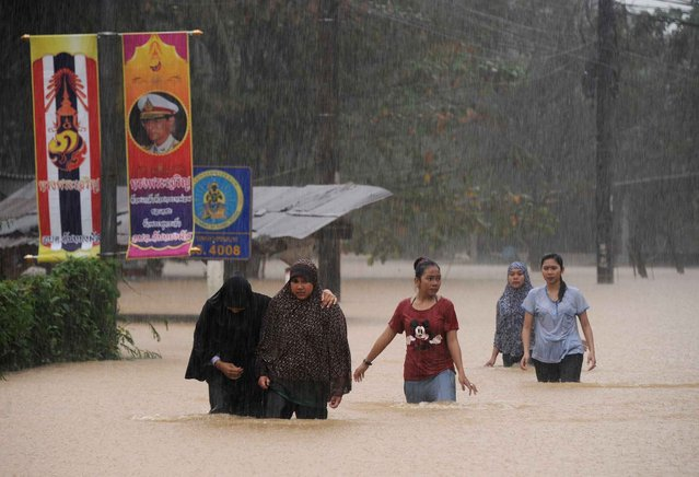 Thai women wade through floodwater after heavy rains triggered flash floods in the Thai southern city of Narathiwat on December 18, 2014. Parts of southern Thailand have experienced floods in recent days after heavy rains hit the region. (Photo by Madaree Tohlala/AFP Photo)