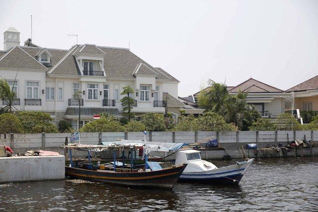 Luxury homes are seen protected behind a seawall in Muara Baru, north Jakarta, September 30, 2014. (Photo by Darren Whiteside/Reuters)