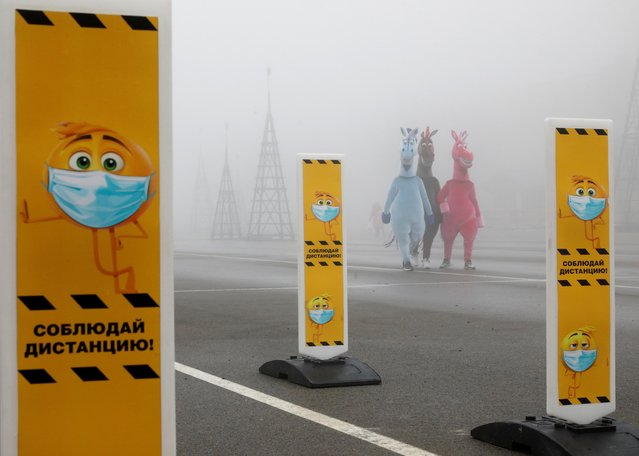 People wearing fancy costumes walk near a skating rink past signs requesting to use protective face masks and to keep a social distance amid the coronavirus disease (COVID 19) outbreak, as heavy fog covers a square named after Soviet state founder Vladimir Lenin in Stavropol, Russia on December 1, 2020. (Photo by Eduard Korniyenko/Reuters)