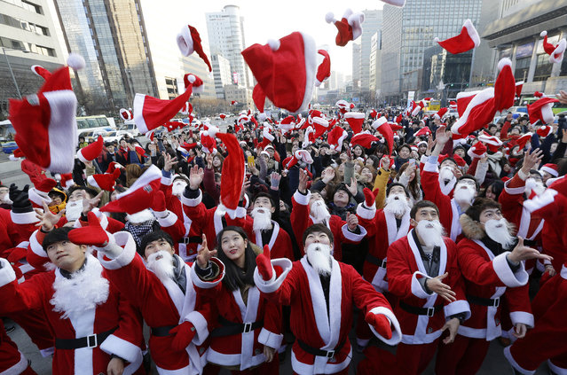 Volunteers clad in Santa Claus costumes throw their hats in the air as they gather to deliver gifts for the poor in downtown Seoul, South Korea, Wednesday, December 24, 2014. (Photo by Ahn Young-joon/AP Photo)