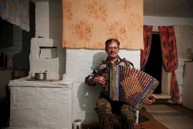 Sergei plays the accordion for Vassa, his partially deaf mother, in their house in the village of Kalach, Sverdlovsk region, Russia. October 18, 2015. (Photo by Maxim Zmeyev/Reuters)
