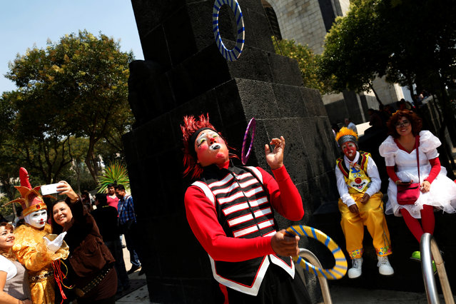 A clown juggles on the street during XXI Convention of Clowns, at the Jimenez Rueda Theatre, in Mexico City, Mexico, October 19, 2016. (Photo by Carlos Jasso/Reuters)