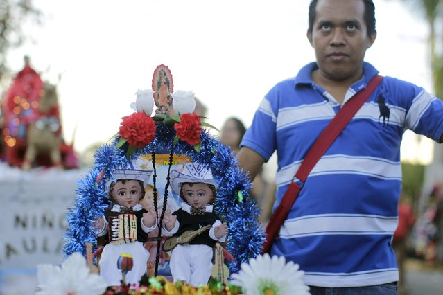 A Catholic man holds figurines of baby Jesus during a religious procession on Holy Innocents Day in Antiguo Cuscatlan, on the outskirts of San Salvador, December 28, 2014. (Photo by Jose Cabezas/Reuters)